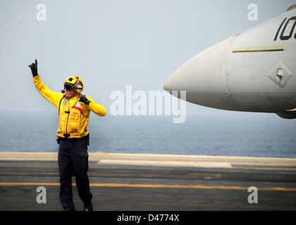 Sailor directs an FA-18F Super Hornet into position aboard USS Ronald Reagan - Stock Photo