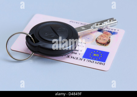 Remote car key with a woman's UK plastic card photographic driving licence on a plain blue background. - Stock Photo