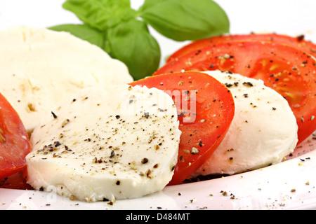 mozzarella and tomato slices with pepper and basilicas. - Stock Photo