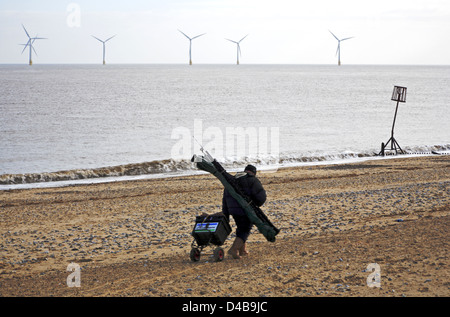 A sea angler on the way to a beach mark at Caister-on-Sea, Norfolk, England, United Kingdom. - Stock Photo