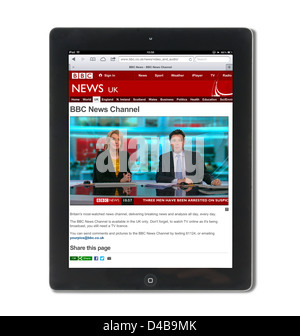 Watching live news on the BBC News channel website on an Apple iPad 4 - Stock Photo
