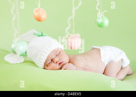 newborn baby dressed in Easter bunny cap - Stock Photo