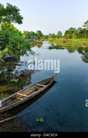 Leaking wooden boat in lagoon with Chinese fishing net in the island of Majuli, Assam, north east India. - Stock Photo