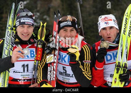 Germans Michael Greis (C), Andreas Birnbacher (L) and French Raphael Poiree celebrate their medals after the 15 - Stock Photo