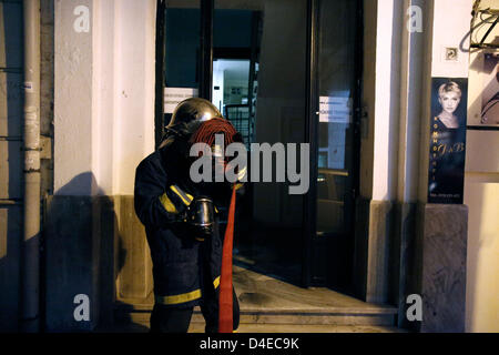 Thessaloniki, Greece. 12th March 2013. Arson attack with gas canisters in the offices of New Democracy MPs. A firefighter - Stock Photo