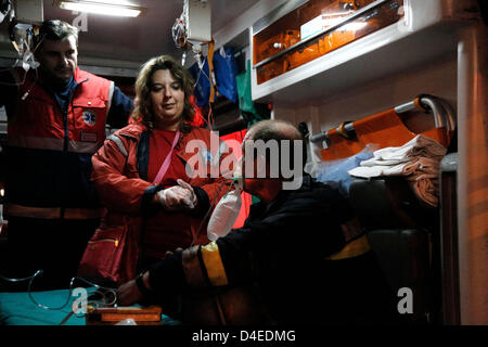 Thessaloniki, Greece. 12th March 2013. Arson attack with gas canisters in the offices of New Democracy MPs. Firefighter - Stock Photo