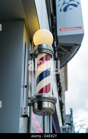 An illuminated barber pole signals the shop is open and ready for business. - Stock Photo