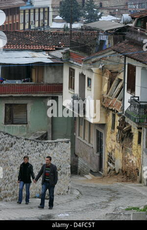 A couple walks through a street in the party destroyed and still closed off Serbian quarter of Prizren, Kosovo, - Stock Photo
