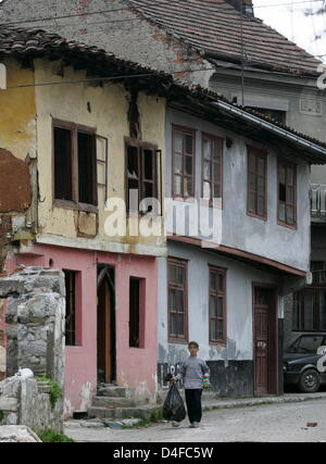 A boy walks down a street in the party destroyed and still closed off Serbian quarter of Prizren, Kosovo, 06 April - Stock Photo