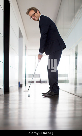 Businessman putting golf ball in office - Stock Photo