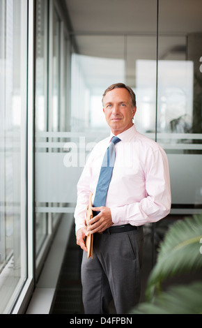 Businessman standing at office window - Stock Photo