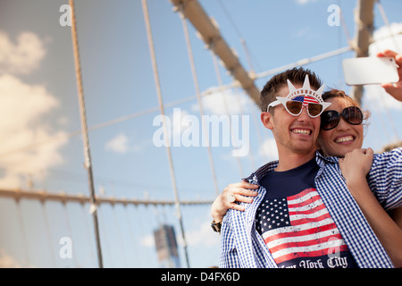 Couple in novelty sunglasses taking picture on urban bridge - Stock Photo