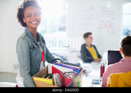 Businesswoman carrying cardboard box of belongings - Stock Photo
