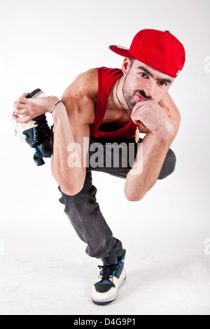 young man bboy sitting serious with red cap on one foot - Stock Photo