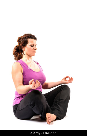 Beautiful woman performs a meditation in the lotus position. - Stock Photo