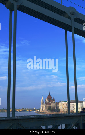 The Hungarian Parliament in Budapest, seen through the chains of the chain bridge - Stock Photo