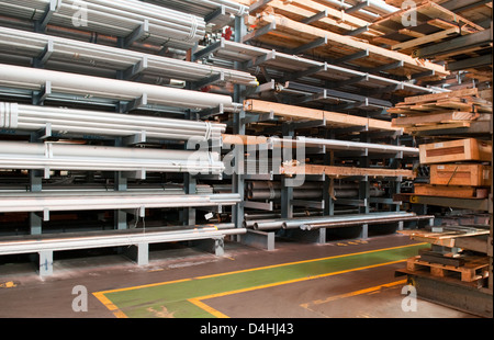 Steel tubes stacked in a warehouse at a steel stock holders in the West Midlands, UK, with a safety walkway painted - Stock Photo