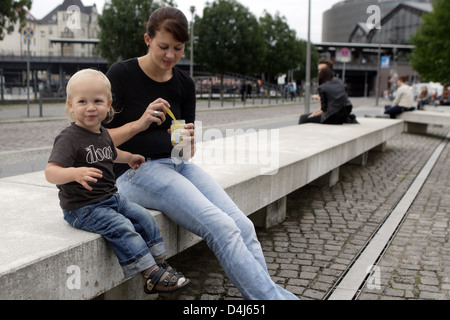 Berlin, Germany, a mother and son sitting on a bench - Stock Photo