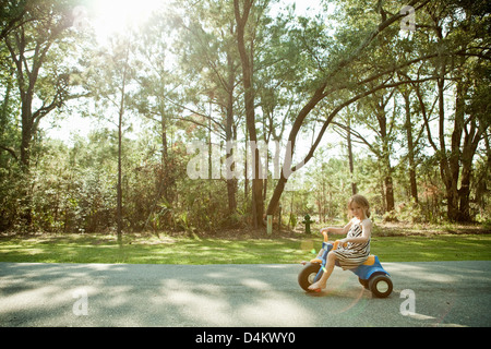 Girl riding toy tricycle on rural road - Stock Photo