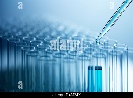 Pipette dropping liquid into test tube - Stock Photo