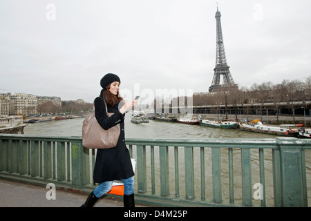 Woman using cell phone on waterfront - Stock Photo