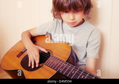 Boy playing guitar indoors - Stock Photo