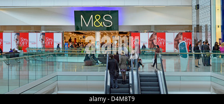 Marks and Spencer shop front with 50% promotion window posters and shoppers on escalators at the Westfield centre - Stock Photo