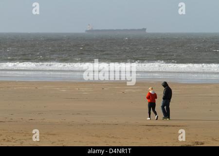 A couple walking in winter on Ballybunion beach, County Kerry, Republic of Ireland - Stock Photo