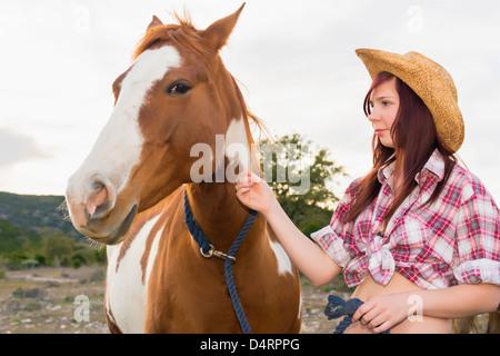 Female teenager petting a horse, Female 19 Caucasian - Stock Photo