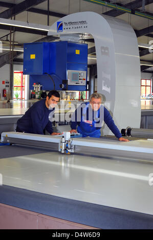 Master Denis Aucio (L) and member of staff Klaus Krumbiegel  (R) operate a high frequency welding machine which - Stock Photo