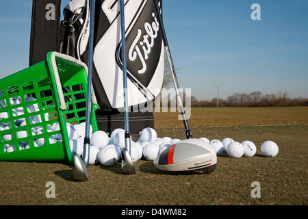 Golf bag and clubs with range balls on a golf practice ground England UK United Kingdom GB Great Britain - Stock Photo