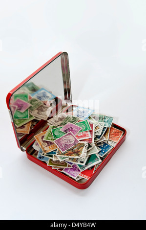 collection of old world postage stamps in red tin with reflection in lid - Stock Photo