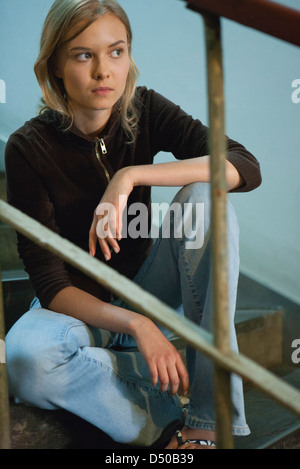 Teenage girl sitting on steps, looking away in thought - Stock Photo
