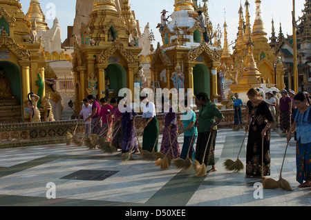 Every evening armies of volunteers sweep the dust from the platform which surrounds the big stupa in Yangon's Shwedagon - Stock Photo