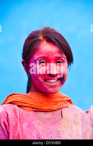 Smiling woman with her face smeared with colors - Stock Photo
