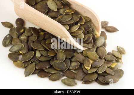 Pumpkin seeds in wooden spoon - Stock Photo