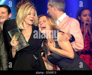English-born singer and actress Olivia Netwon-John (L) smiles with her Radio Regenbogen Award and German TV host - Stock Photo