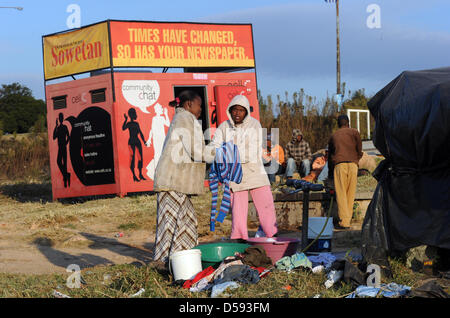 South African women wash clothes at the roadside in the Soweto township near Johannesburg, South Africa, 09 June - Stock Photo