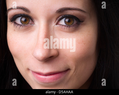 Close up portrait of happy young woman wearing make up - Stock Photo