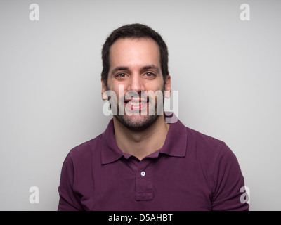 Portrait of a 3-day bearded young man with fake smile - Stock Photo