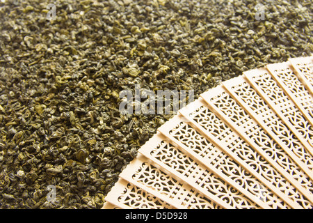 Green tea background with wooden fan close up. Selective focus. - Stock Photo
