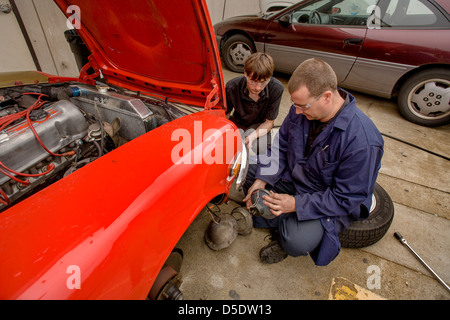 A teenage boy talks with his teacher teacher as they work together outdoors on a car in auto shop class in San Clemente, - Stock Photo