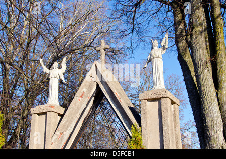 two ancient angels statues on old gate in park - Stock Photo