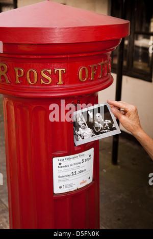 England, Berkshire, Eton High Street, posting Royal family postcard in historic 1856 Victorian post pillar box - Stock Photo
