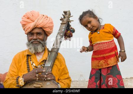 Musician holding a sitar with his young daughter dancing at the Pushkar Mela, Pushkar, Rajasthan, India - Stock Photo