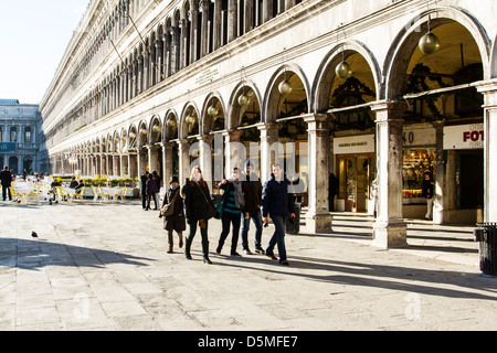 Tourists in Saint Mark Square (Piazza San Marco) and Doge's Palace (Palazzo Ducale) behind. - Stock Photo