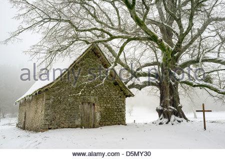 The small chapel at Le Mas Saint-Jean on a snowy winter day, Saint-Sulpice-le-Dunois, La Creuse, Limousin, France - Stock Photo
