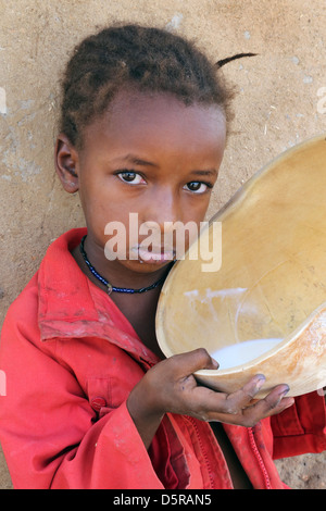 Girl drinks cow's milk from a calabash, Burkina Faso - Stock Photo