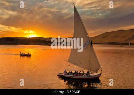 Traditional wooden sailing boats or Feluccas at sunset sailing on the river Nile at Aswan Egypt Middle East - Stock Photo