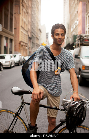 Man on bicycle on city street - Stock Photo
